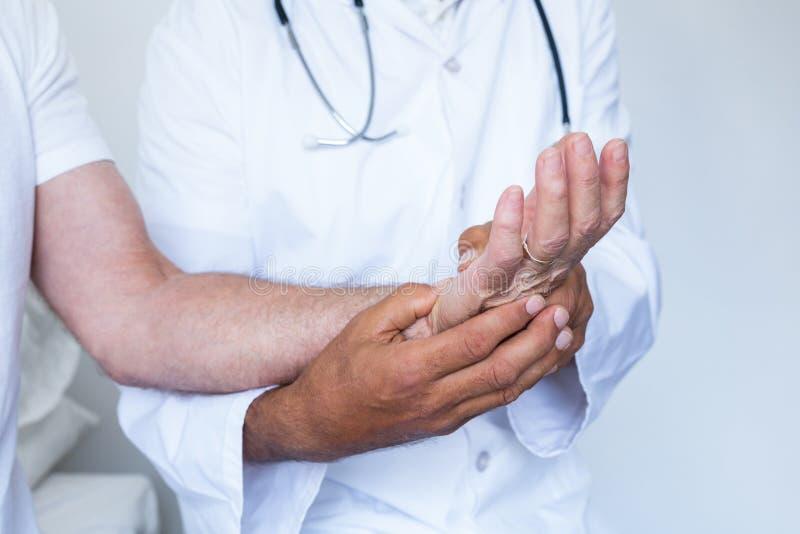 Мужской доктор давая обработку точечного массажа ладони к пациенту стоковое фото rf