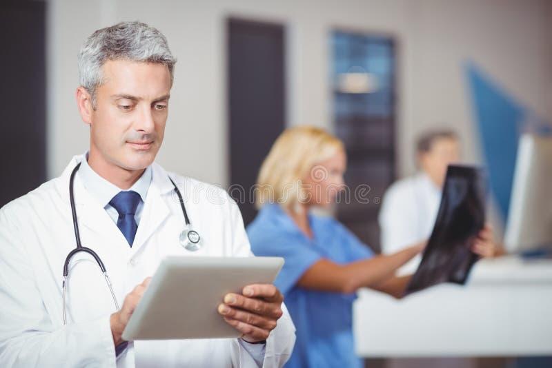 Мужской доктор используя цифровую таблетку при коллега проверяя рентгеновский снимок стоковые фото