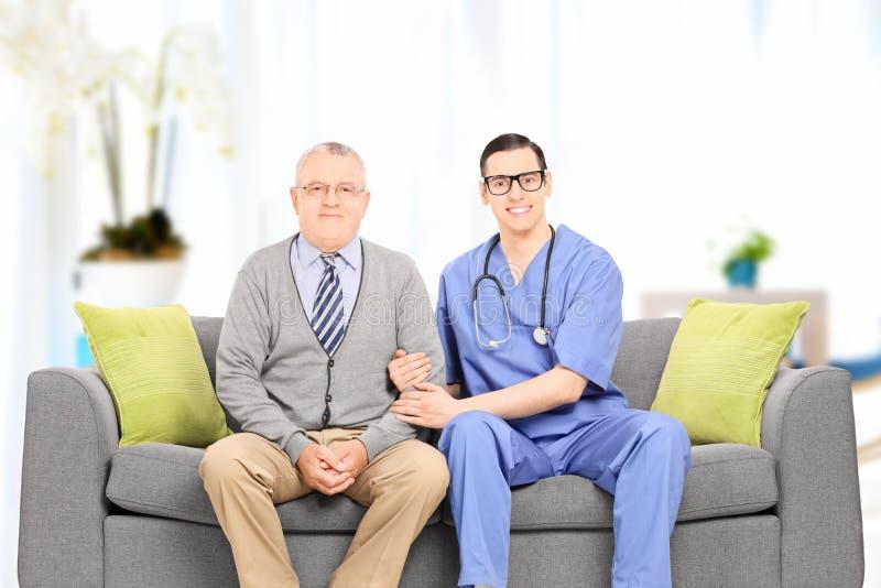 Мужской доктор и пожилой джентльмен усаженные на софу стоковые изображения