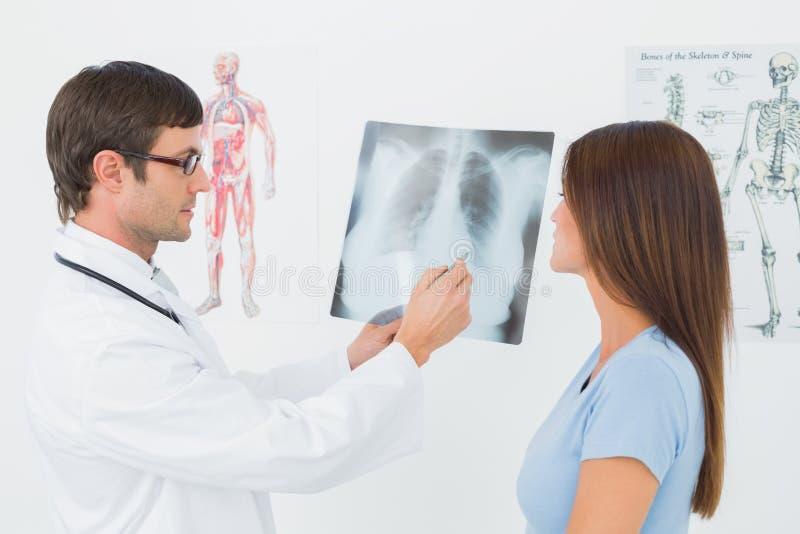 Мужской доктор объясняя рентгеновский снимок легких к женскому пациенту стоковое фото