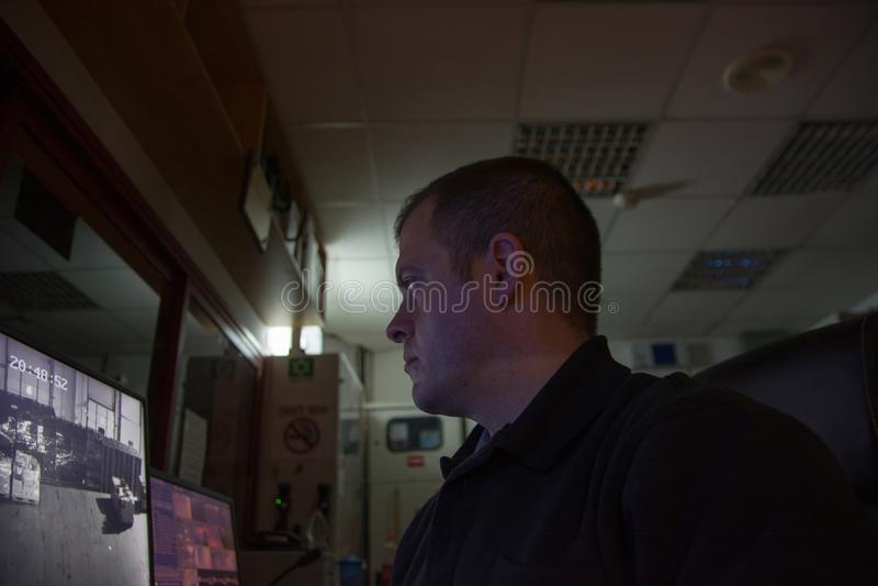 Мужской охранник на рабочем месте смотрит ligth монитора низкое стоковые изображения