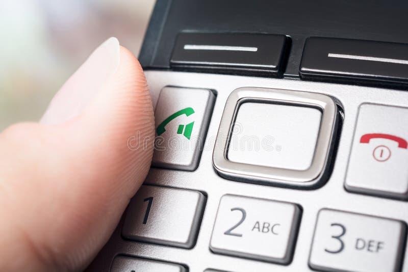 Мужской палец на кнопке звонка беспроволочные DECT Telefphone, подготавливает для того чтобы набрать или активировать функцию гро стоковая фотография rf