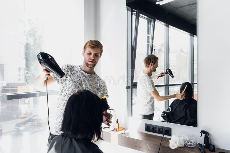 Мужской парикмахер усмехаясь и разговаривая с клиентом пока делающ новую стрижку к красивой молодой женщине брюнет стоковые фотографии rf