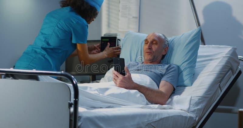 Мужской пациент используя видео- звонок в палате стоковое изображение rf