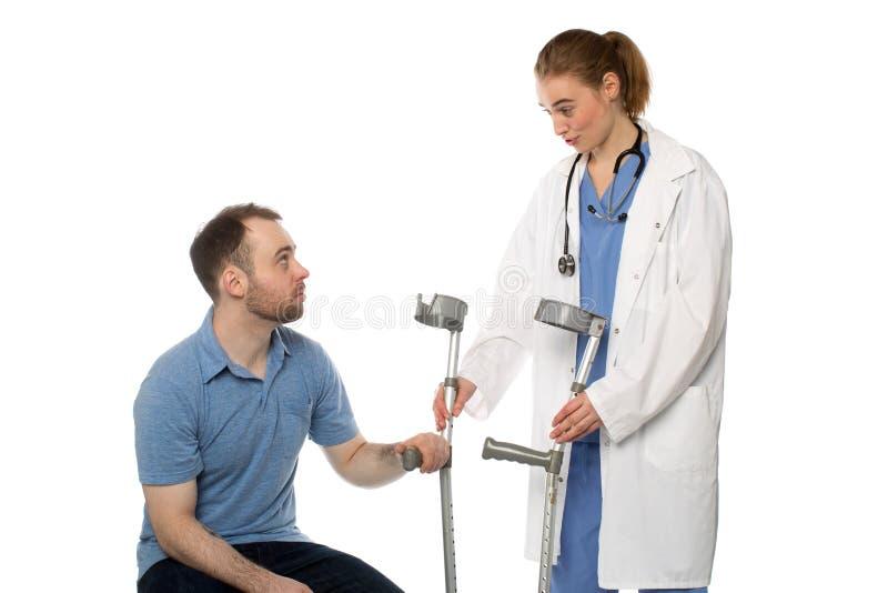 Мужской пациент получает костыли от доктора женщины стоковое фото rf