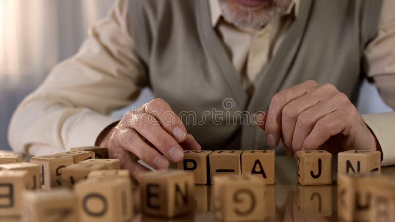 Мужской пенсионер пробуя сделать слово из деревянных кубов, слабоумие старости, реабилитацию стоковое фото