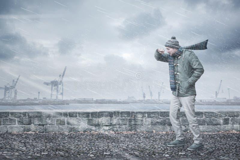 Мужской пешеход смотрит на сильный ветер и дождь стоковое изображение rf
