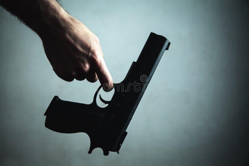 Мужской пистолет удерживания руки Уголовная концепция стоковое фото