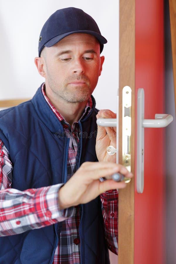 Мужской плотник разнорабочего работника на установке замка в деревянную дверь стоковое изображение rf