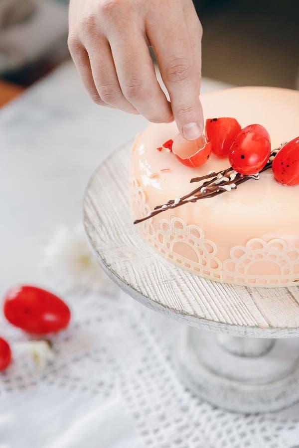 Мужской повар украшает торт печенья с яйцом шоколада для пасхи Светлая белая гамма стоковое фото rf