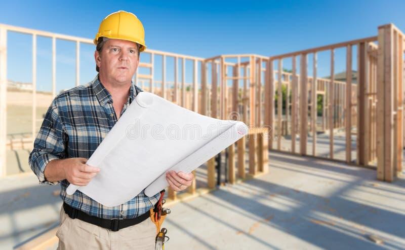 Мужской подрядчик при планы дома нося трудную шляпу внутри нового дома стоковая фотография rf