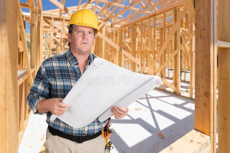 Мужской подрядчик при планы дома нося трудную шляпу внутри нового Hou стоковая фотография rf