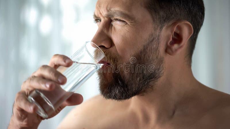 Мужской полоща зуб с водой, гиперчувствительностью, острой зубоврачебной болью, воспалением десен стоковое фото