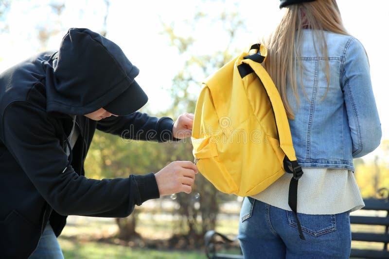 Мужской похититель пробуя украсть деньги от молодой женщины в парке стоковое фото rf