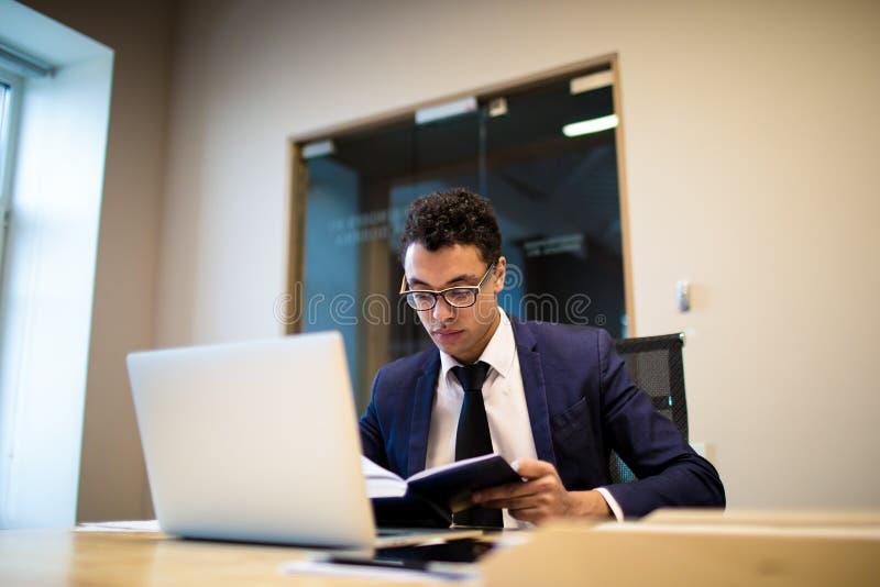 Мужской предприниматель подготавливая к встрече штата, используя netbook и тетрадь стоковая фотография