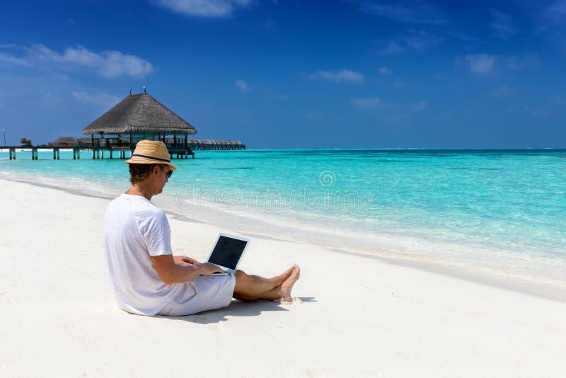 Мужской предприниматель работает на тропическом пляже стоковые изображения rf