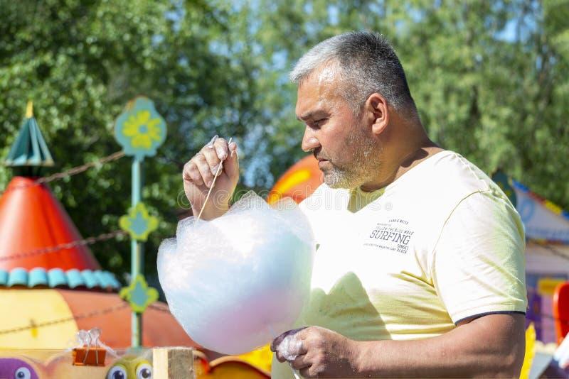 Мужской продавец держит сладкую конфету хлопка в его руке стоковое изображение rf