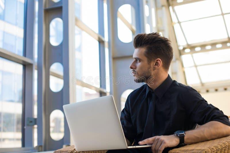 Мужской профессиональный писатель мечтая во время работы на netbook Задумчивый главный исполнительный директор в костюме стоковое изображение
