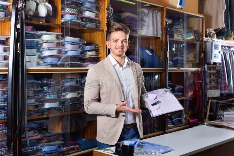 Мужской продавец демонстрируя рубашки в магазине одежды men's стоковая фотография rf