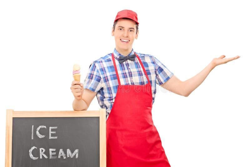Мужской продавец мороженого показывать с рукой стоковое фото rf