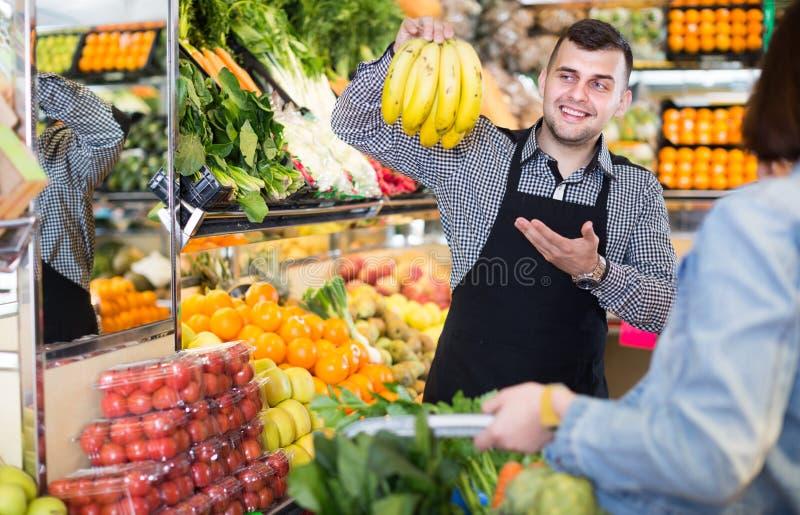 Мужской продавец помогая в покупать стоковая фотография