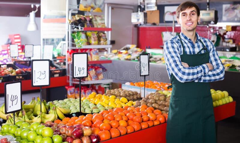 Мужской продавец представляя с яблоками, tangerines и бананами в магазине стоковое изображение rf