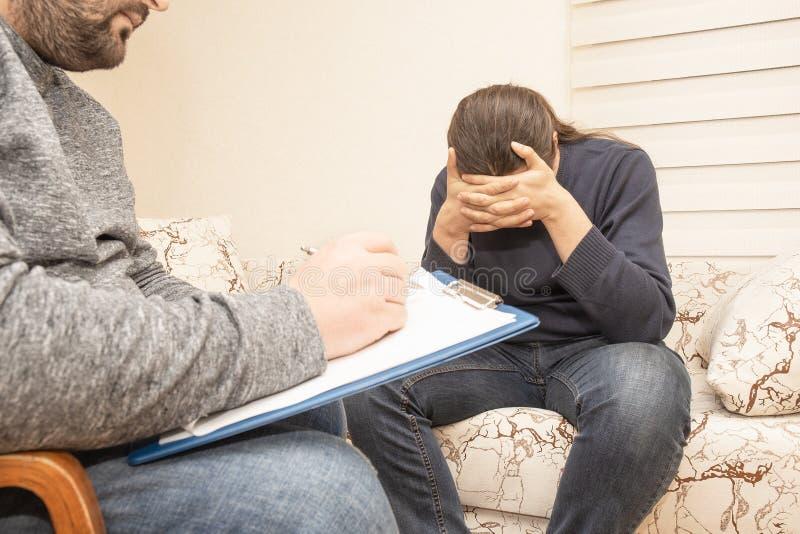 Мужской психолог советуя с унылым упадочным человеком на психологической терапевтической сессии, консультации психолога и умствен стоковое фото rf