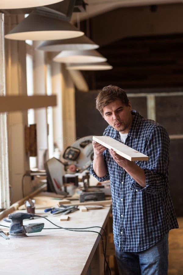 Мужской плотник в мастерской плотничества дует обломоки с деревянной горжеткой стоковое фото rf