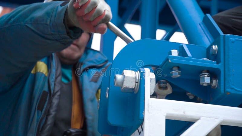 Мужской работник затягивая болты и ключ в конструкции r Деятельность человека принималась за установку металла стоковая фотография rf