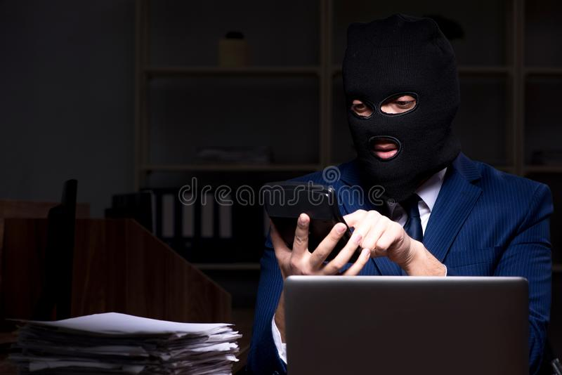 Мужской работник крадя информацию в nighttime офиса стоковое изображение