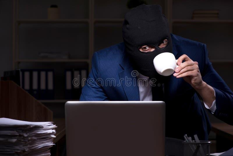 Мужской работник крадя информацию в nighttime офиса стоковое изображение rf