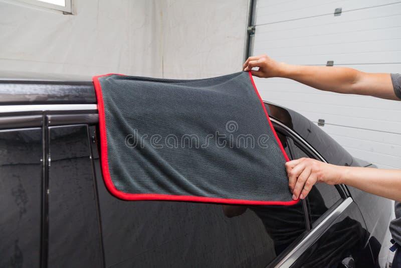 Мужской работник моет черный автомобиль, обтирая воду с мягкими тканью и microfiber, очищая поверхность для того чтобы посветить  стоковое изображение