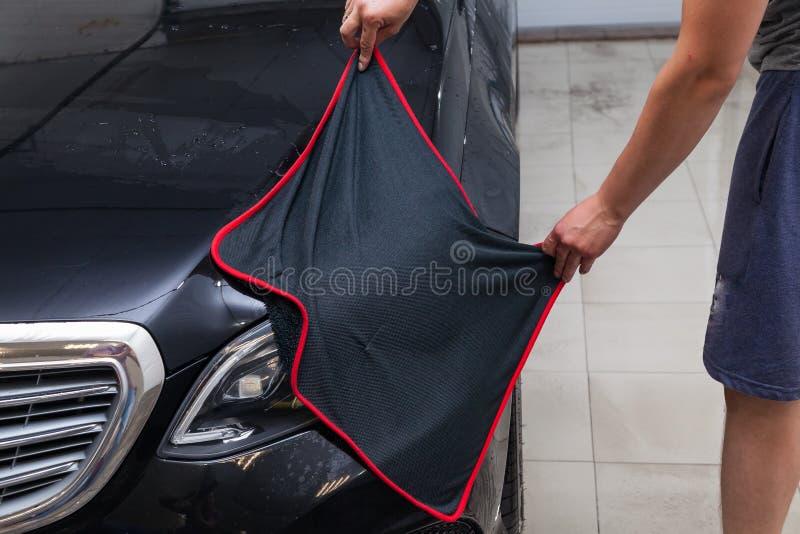 Мужской работник моет черный автомобиль, обтирая воду с мягкими тканью и microfiber, очищая поверхность для того чтобы посветить  стоковое фото