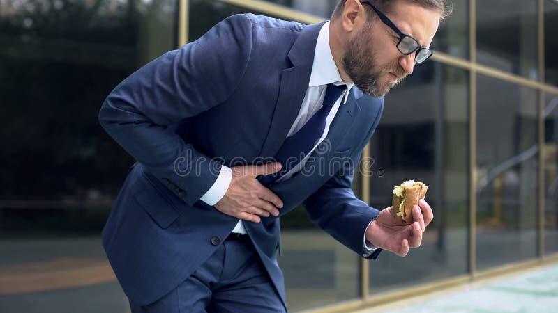 Мужской работник офиса есть гамбургер фаст-фуда, чувствуя боль в животе, гастрит стоковая фотография