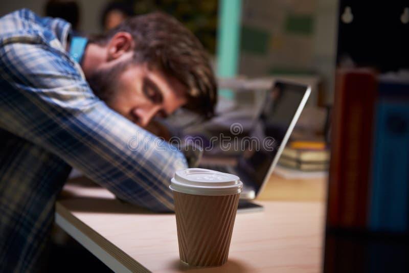 Мужской работник офиса уснувший на столе работая поздно на компьтер-книжке стоковое изображение