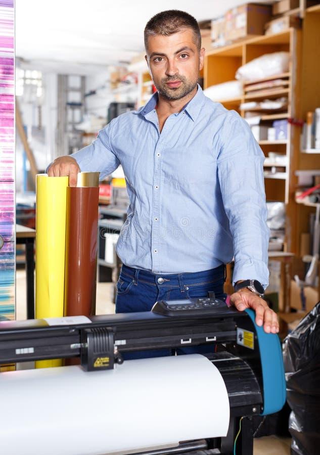 Мужской работник рекламного бюро с склеивающими пленками стоковое фото