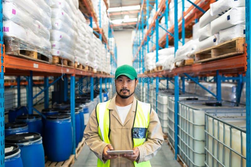 Мужской работник смотря камеру пока работающ в складе стоковая фотография