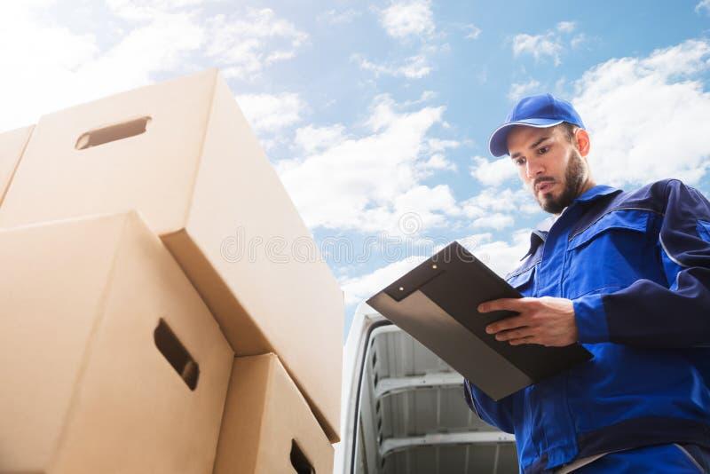 Мужской работник стоя близко картонная коробка держа доску сзажимом для бумаги стоковые изображения rf