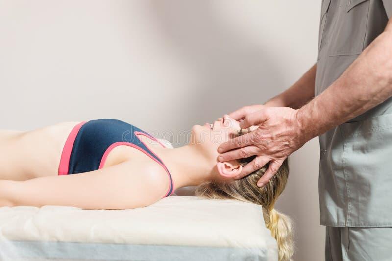 Мужской ручной висцеральный masseur терапевта обрабатывает молодого женского пациента Массаж головы и уха стоковые изображения rf