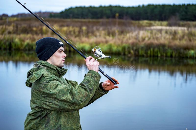 Мужской рыболов зацепляет закручивая рыба в холодной воде в offseason стоковые фотографии rf