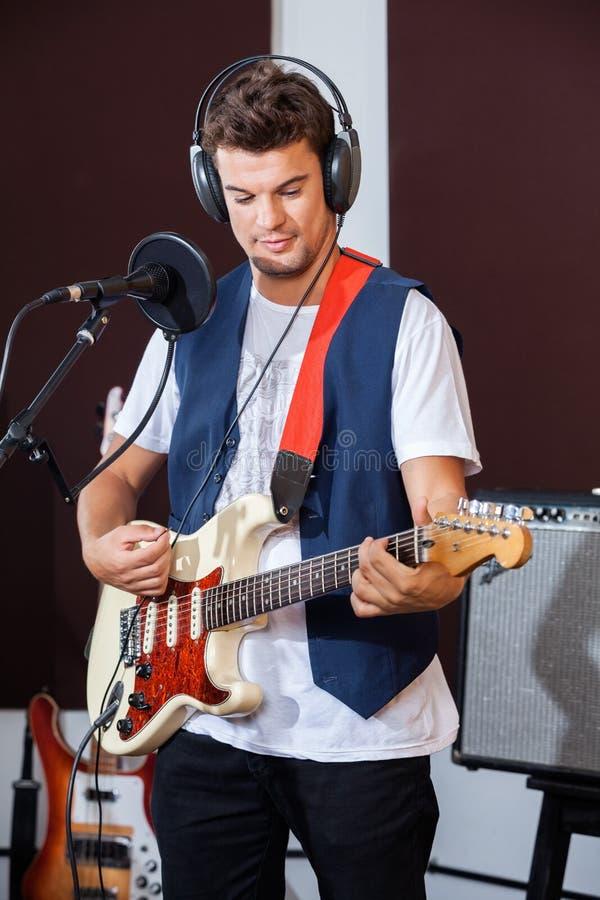 Мужской совершитель играя электрическую гитару в студии стоковое изображение rf
