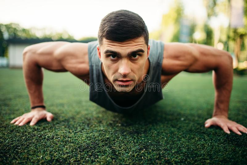 Мужской спортсмен делая тренировку нажима-вверх внешнюю стоковое фото