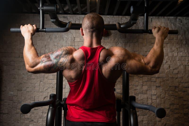 Мужской спортсмен культуризма делая тягу поднимает стоковая фотография rf