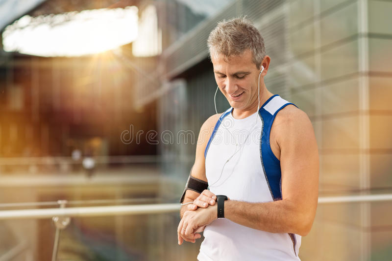 Мужской спортсмен смотря вахту стоковое изображение rf