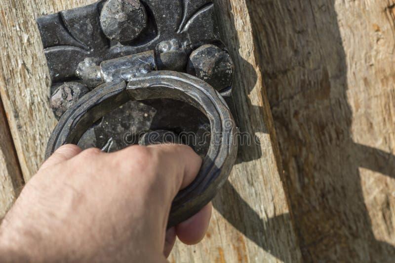 Мужской стук руки с старым черным knocker двери на деревянной и деревенской двери стоковые фотографии rf