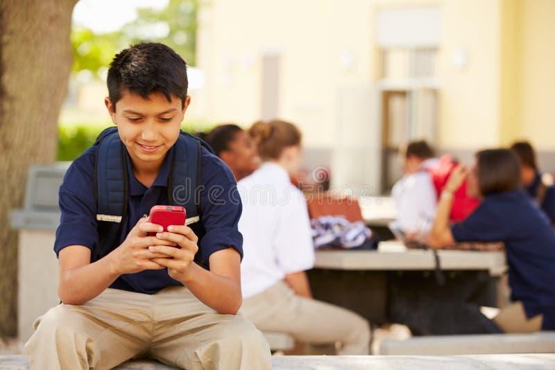 Мужской студент средней школы используя телефон на кампусе школы стоковые изображения rf