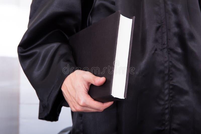 Мужской судья держа книгу по праву стоковое изображение
