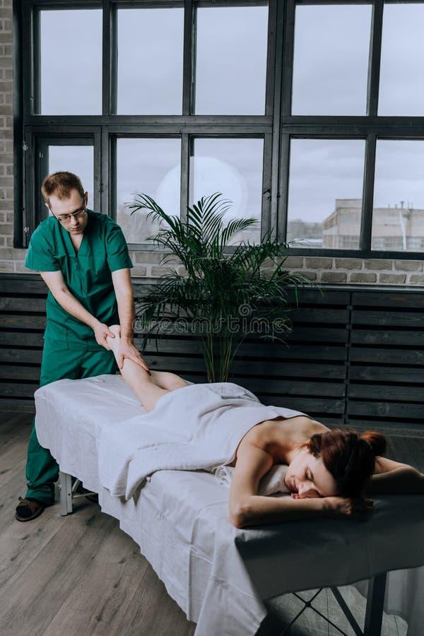 Мужской терапевт массажа массажирует молодую женщину, метод протягивать стоковые фотографии rf
