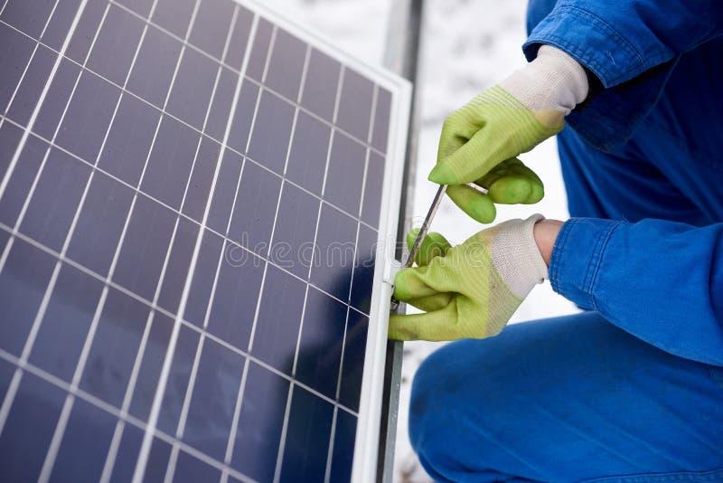 Мужской техник в голубом костюме устанавливая фотовольтайческие голубые солнечные модули с винтом стоковая фотография rf