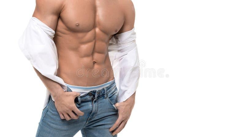 Мужской торс с идеальным abs Человек в голубых джинсах и белой рубашке изолированных на белизне стоковое изображение rf